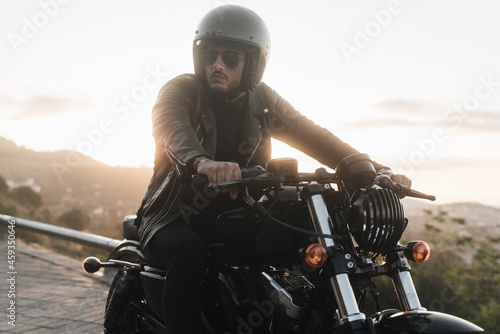 Tableau sur Toile Lifestyle portrait of young stylish biker sitting on his vintage motorcycle, wea