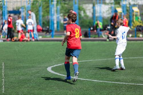 Fotografie, Obraz Teenager in red sportswear plays football on field, dribbles ball