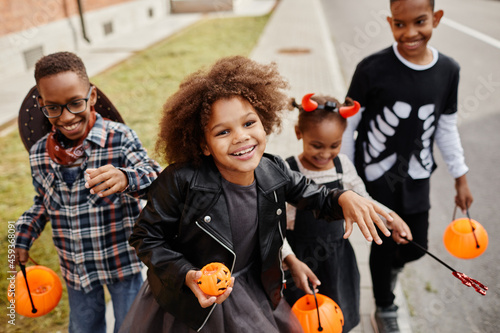 Obraz na płótnie Group of smiling African-American kids trick or treating outdoors and walking to