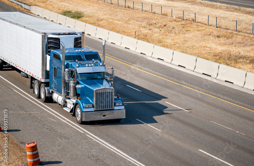 Fotografie, Obraz Classic idol blue big rig semi truck with chrome parts and cab with truck driver