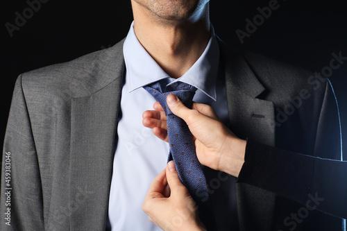 Fotografia Woman fixing man's tie on dark background
