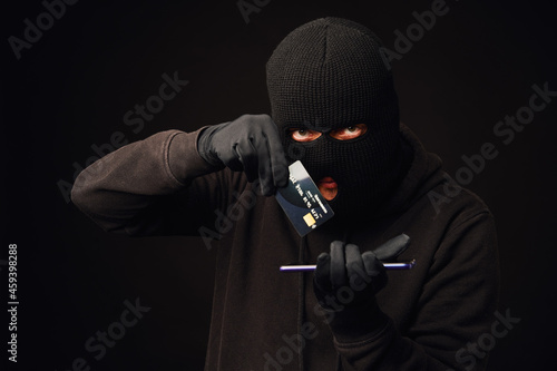 Fotografia Anonymus thief holding credit card and phone