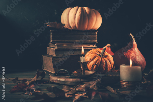 Photo Still life for Halloween and Thanksgiving with old books, pumpkins and candle