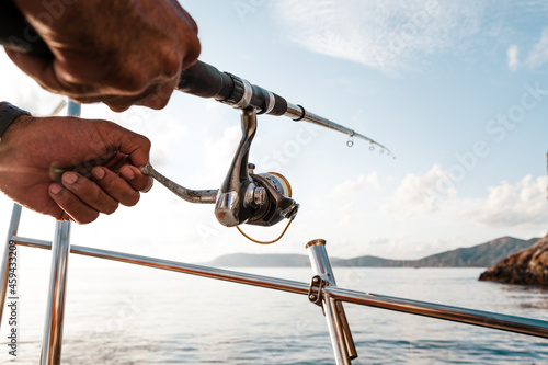 Canvas Close up of male hands holding fishing rod while fishing on sailboat in open sea