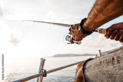 Obraz na plátně Close up of male hands holding fishing rod while fishing on sailboat in open sea