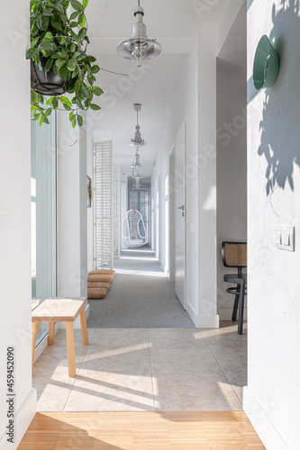 Fototapeta Long white corridor with modern lightning, wooden furniture, green plant and arm
