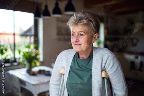 Foto Portrait of senior woman with crutches indoors at home, looking aside
