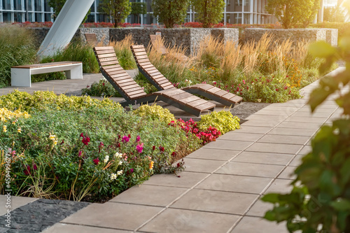 Two empty brown wooden deck chairs or chaise longues on tile among decorative grass and flowers in recreation area Fotobehang