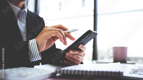 Fotografija Businesswoman or accountant using the phone to check business information