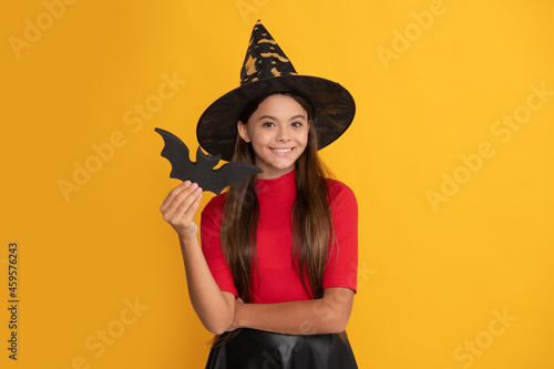 Obraz na plátně smiling kid with bat wearing witch hat on yellow background, halloween