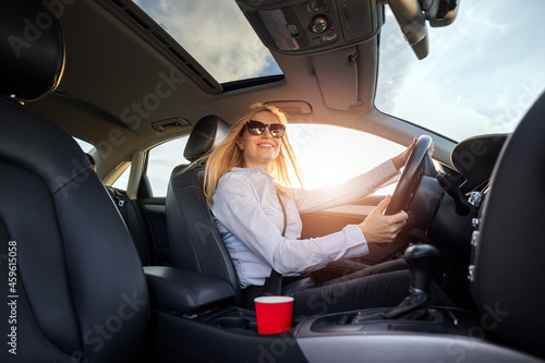 Photo Happy caucasian woman with blond hair driving modern car during sunny day
