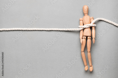 Fotografie, Obraz Mannequin with tied around rope on grey background