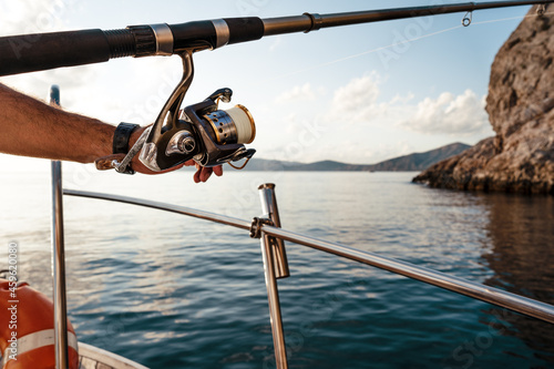 Fototapeta Close up of male hands holding fishing rod while fishing on sailboat in open sea