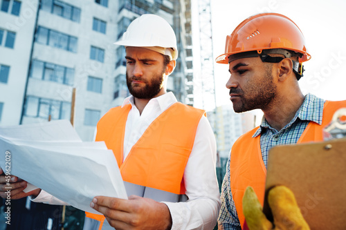Canvas Print Two young male engineers in uniform and hardhats working at construction site