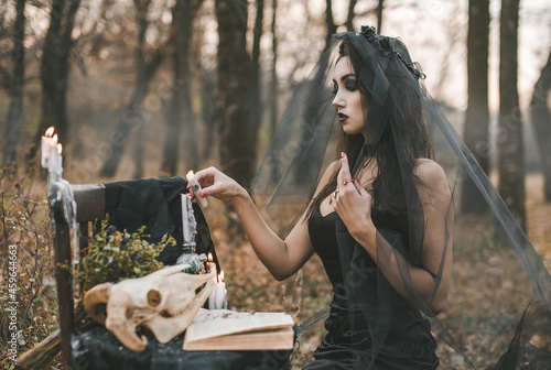 Brunette witch girl conjures in the forest conducts rituals with a fantasy skull Fototapeta