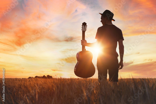 Obraz na plátně play music, silhouette of musician with guitar at sunset field outside