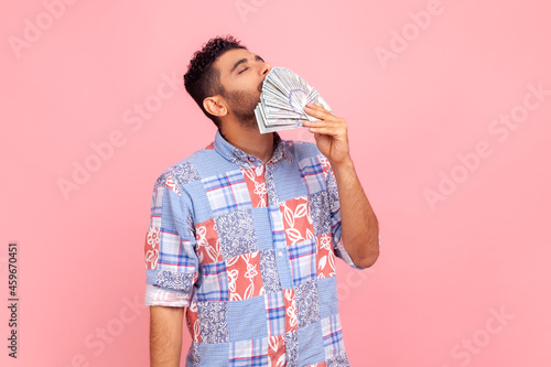 Fotografia, Obraz Portrait of handsome greedy arrogant man with beard smelling dollar banknotes with expression of pleasure, crazy about money, wealthy life