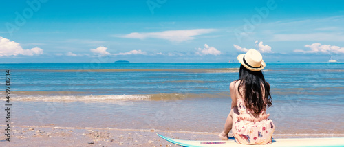 Fotografia Surfer girl on the beach holding surf board watching ocean in sunny day