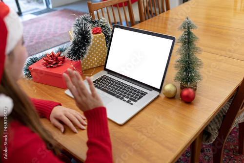 Caucasian woman wearing santa hat having video call on laptop with copy space at christmas time