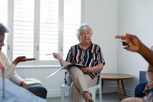 Caucasian senior female counsellor in face mask advising diverse group of senior friends