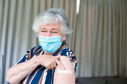 Senior caucasian woman in face mask showing plaster after vaccination