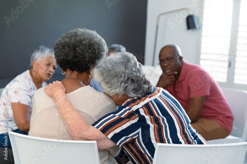 Back view of caucasian senior woman embracing african american female friend and supporting her