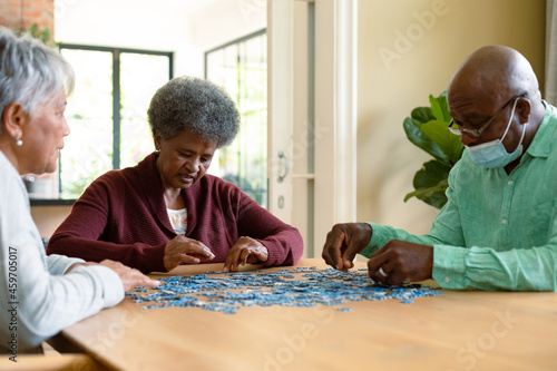 Two diverse senior women and african american male friend wearign face mask doing puzzles
