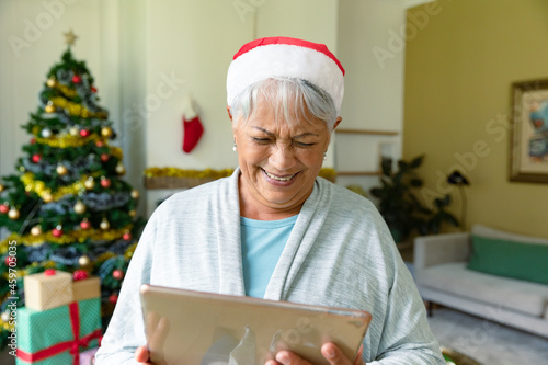 Happy mixed race senior woman in santa hat using tablet at christmas time