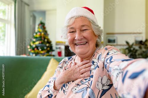Happy caucasian senior woman wearing santa hat having video call at christmas time