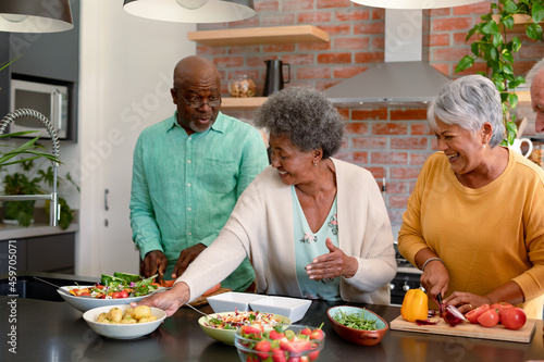 Group of happy diverse senior male and female friends cooking together at home