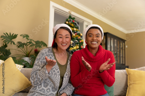 Two happy diverse female friends in santa hats having video call at christmas time