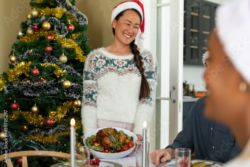 Happy asian woman in santa hat holding dish, celebrating christmas with friends at home