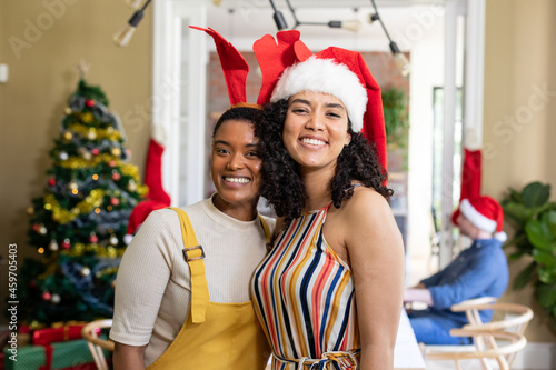 Two diverse female friends in santa hats embracing, taking photo, celebrating christmas at home
