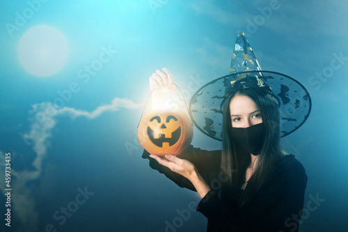 halloween witches party in covid,magical sorceress in a mask with a burning pump Fototapeta