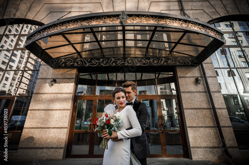 Fotografering bride and groom in a dress in front of the hotel