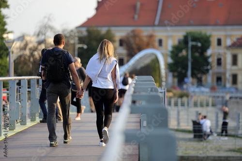 Para młodych ludzie, kobieta i mężczyzna spaceruje po moście we Wrocławiu.