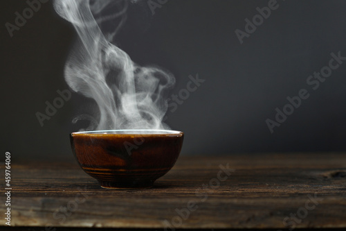 Tela bowl of hot soup with steaming on wooden table on black background