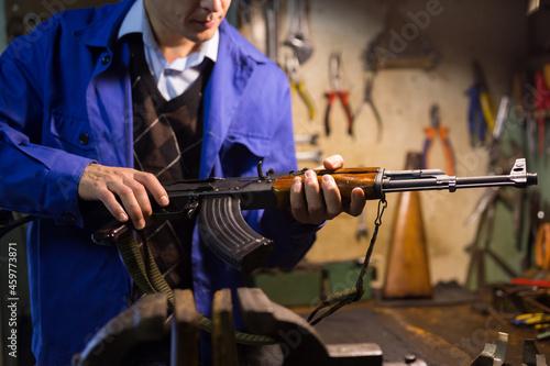 Obraz na plátně Closeup of Kalashnikov assault rifle in hands of gunsmith