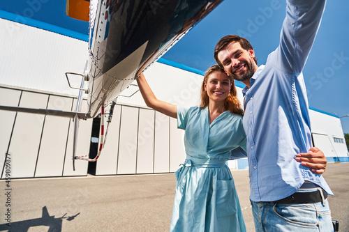 Billede på lærred Romantic couple standing by chopper parked on helipad