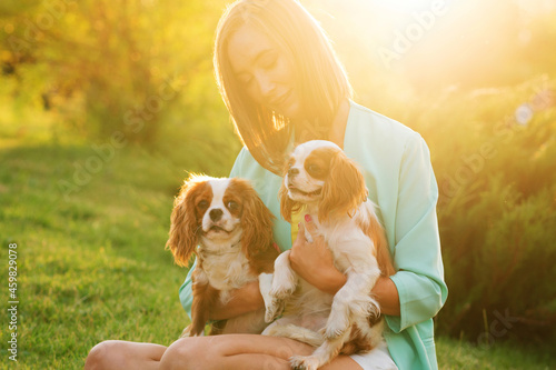 Caring breeder walks at sunset with two purebred pets Fototapet