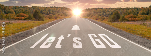 Fotografia word let's go written on highway road in the middle of empty asphalt road at beautiful sunset sky