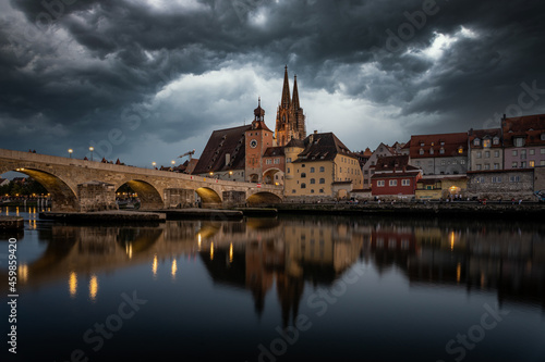 Tableau sur Toile View from the Danube on the Regensburg Cathedral and Stone Bridge with lights in