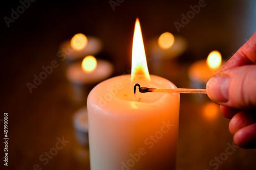 Obraz na plátně Light candle with match dark background lighting, hand with match