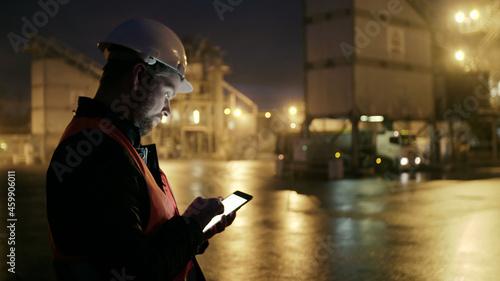 Fotografie, Obraz Engineer in hardhat checking loading of truck wit tablet computer