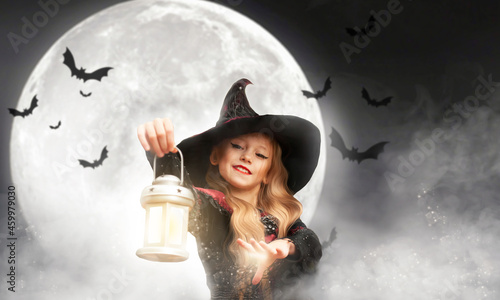 Fotografia a girl in a witch costume holds a lantern conjuring over him against the background of the moon on Halloween