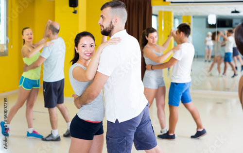 Positive men and women dancing salsa in dance hall Fototapeta