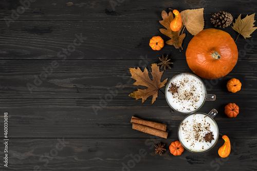 Billede på lærred Spice pumpkin latte with cream foam, cinnamon stick, leaf and orange pumpkins on wooden background, copy space