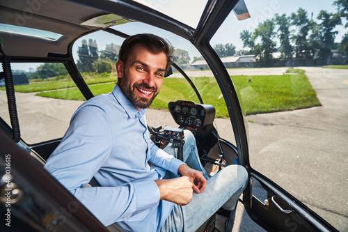 Slika na platnu Joyful airman posing for camera in helicopter cabin