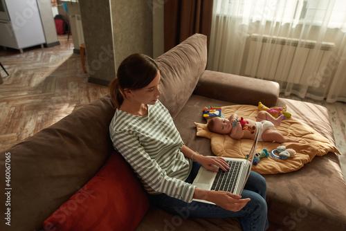 Fototapeta Mother browsing Internet sitting near cute infant baby