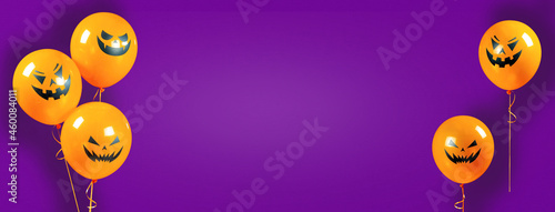 Halloween banner on purple background with copy space. Orange helium balloons with scary laughing pumpkin faces on a long purple banner for holiday posters, Halloween sales.
